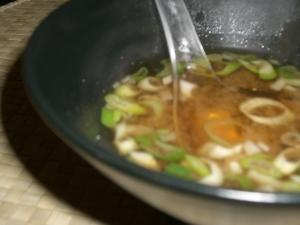 Bol en céramique asiatique noire contenant une portion de soupe  miso