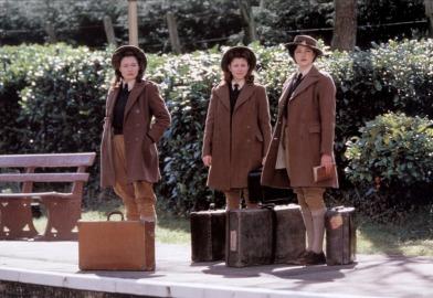 trois écolières anglaise à l'ancienne sur un quai de gare avec des valises